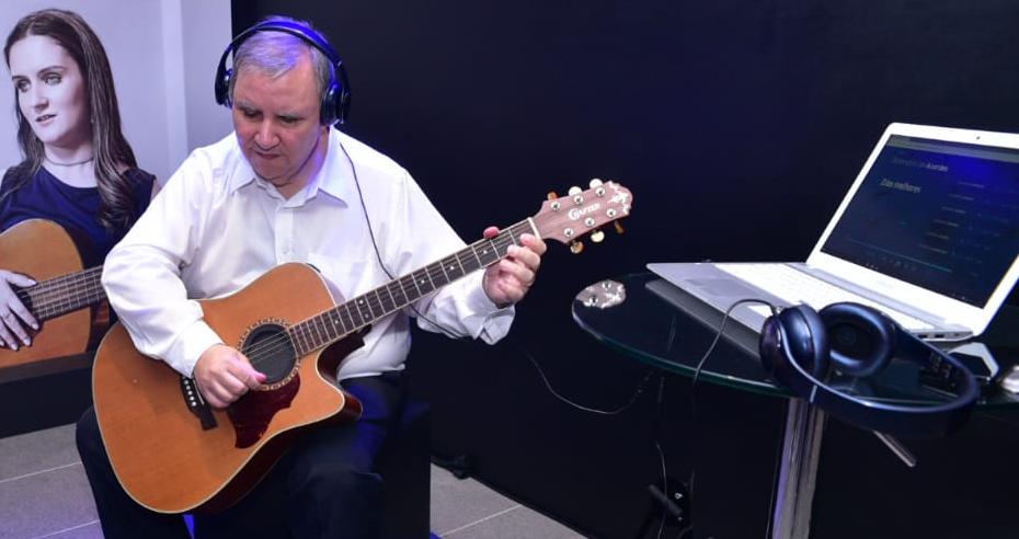 Pessoa tocando o violão e utilizando fone de ouvido