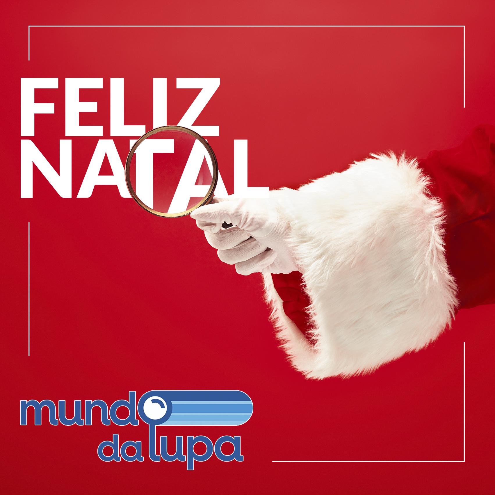 A mão do Papai Noel está segurando uma lupa, ampliando a mensagem de Feliz Natal