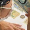 mulher com a lupa de cabeça analisando uma nota antiga