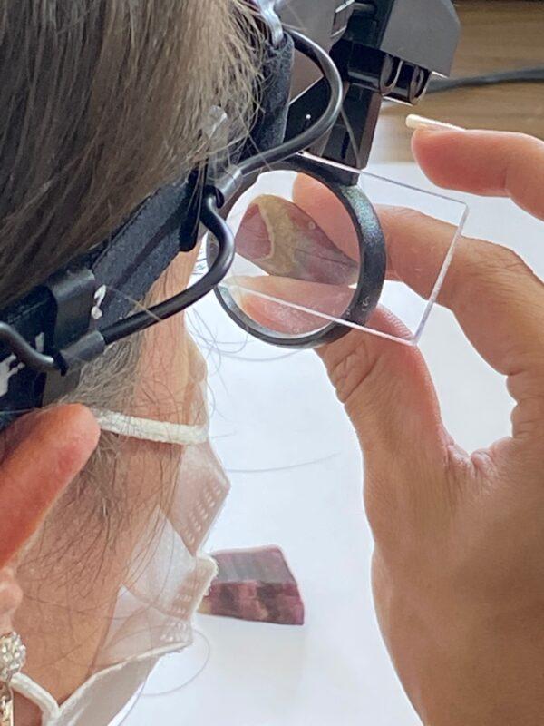 mulher examinando a pedra com a lupa de cabeça
