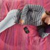 jovem deitada na cama com forne de ouvido olhando para o Victor Reader Stream