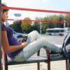 Jovem no ponto de ônibus com seu leitor digital Victor Reader Stream