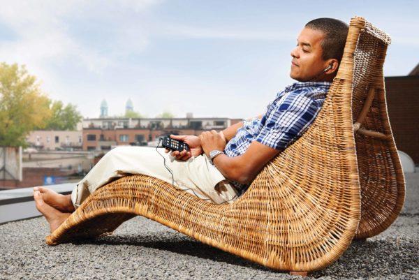 Homem deitado na espreguiçadeira segurando seu leitor digital Victor Reader Stream