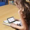 estudante lendo livro ampliado através da lupa explore 5
