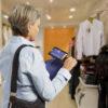 mulher na loja de roupas vendo a etiqueta através da sua lupa explore 5